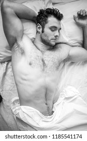 Handsome man with abs, muscular, hunky body and beard lies naked in between white sheets on bed..