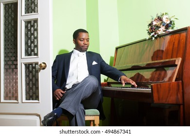 Handsome man african American groom in elegant suit with white tie and handkerchief pocket square for wedding ceremony plays piano