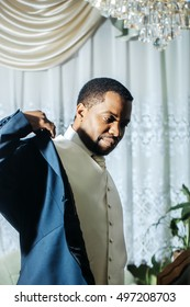 Handsome man african American groom puts on elegant suit coat for wedding ceremony