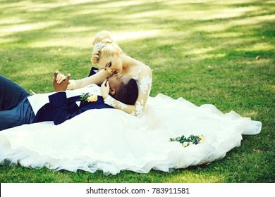 Handsome man or african American groom lying in arms of pretty girl or cute bride with beautiful blond hair in white wedding dress sitting on green grass on sunny summer day on natural background