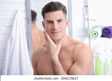 Handsome man after shaving in bathroom