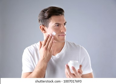 Handsome man applying face cream on grey background