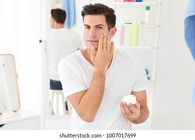 Handsome man applying face cream in bathroom