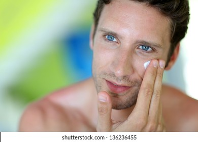 Handsome man applying moisturizing cream