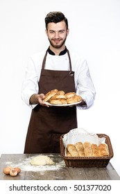 Handsome man in apron with fresh bakery isolated on white background. Chef offers a ready-made pastries to the viewer