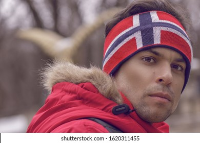 Handsome man athlete in a red jacket and a hat on his head with the flag of Norway, in winter, turned his head back looking into the frame