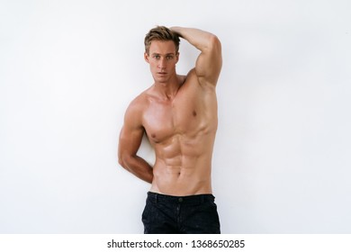 Handsome man in athletic uniform on white background. Fitness model posing in black pants.