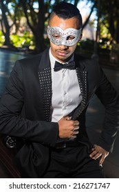 handsome man attending a masquerade ball sitting on a bench and hiding something in his pocket