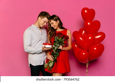 Handsome man and attractive woman looking at box with gift, red roses, balloons while celebrating a St. Valentine's day.