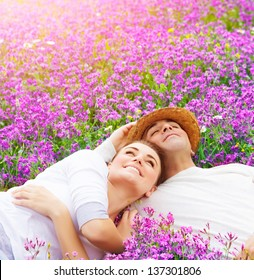 Handsome man with attractive woman lying down on fresh lavender field, enjoying each other, romantic relationship, love concept