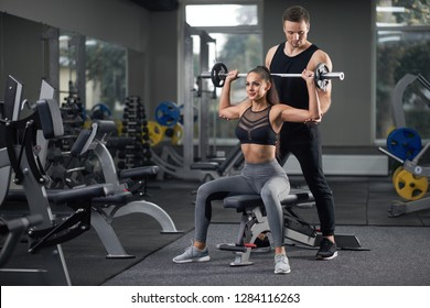 Handsome man and attractive woman smiling looking away and keeping fit with trainer. Young man holding arms and helping her with it. Concept of healthy lifestyle and sport activity.