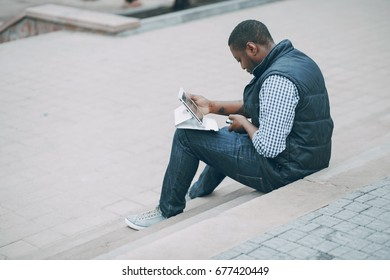 handsome man in autumn city with tablet and phone