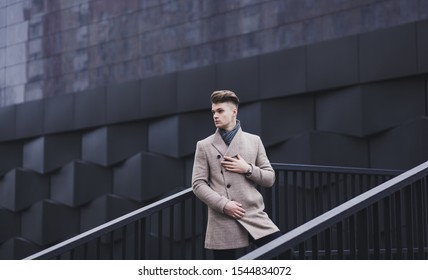 handsome man in autumn coat on the background of urban environment