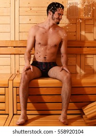 Handsome man or bather with muscular sexy torso, body, wet with big splash of water in sauna, thermal bath on wooden background