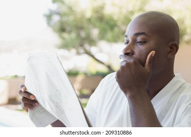 Handsome man in bathrobe reading newspaper outside on a sunny day