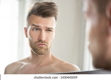 handsome man in the bathroom looks at himself in the mirror and grimaces