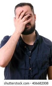 handsome man with a beard covers his face with hands isolated on white background