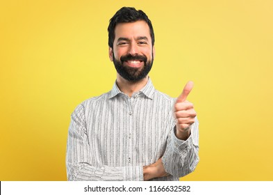 Handsome man with beard giving a thumbs up gesture and smiling
