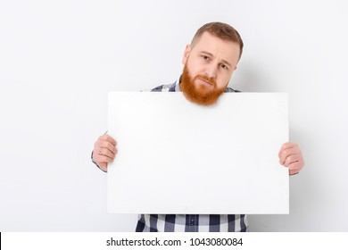 handsome man with beard holding big white card. empty blank board