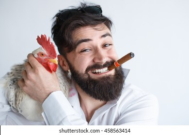 Handsome man with beard holding a chicken. Selling a cock concept. Male making crazy selfie with his pet bird