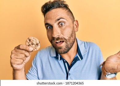 Handsome man with beard holding cookie celebrating achievement with happy smile and winner expression with raised hand