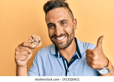 Handsome man with beard holding cookie smiling happy and positive, thumb up doing excellent and approval sign
