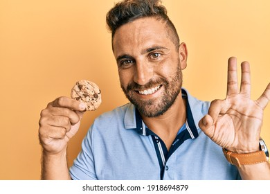 Handsome man with beard holding cookie doing ok sign with fingers, smiling friendly gesturing excellent symbol