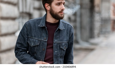 A handsome man with a beard in a jeans jacket on the street smoking