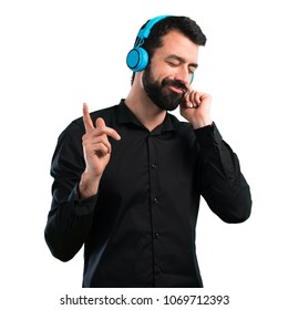 Handsome man with beard listening music on white background