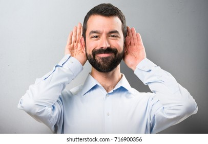 Handsome man with beard listening something on textured background