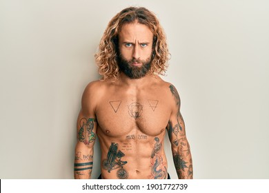 Handsome man with beard and long hair standing shirtless showing tattoos skeptic and nervous, frowning upset because of problem. negative person.
