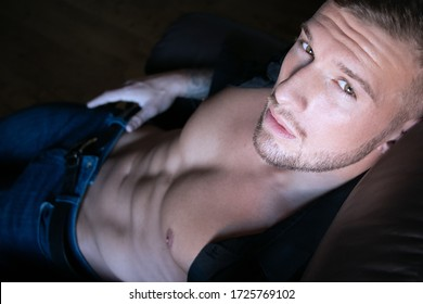 Handsome man with beard and open shirt revealing muscular abs sitting in leather armchair looking at camera.