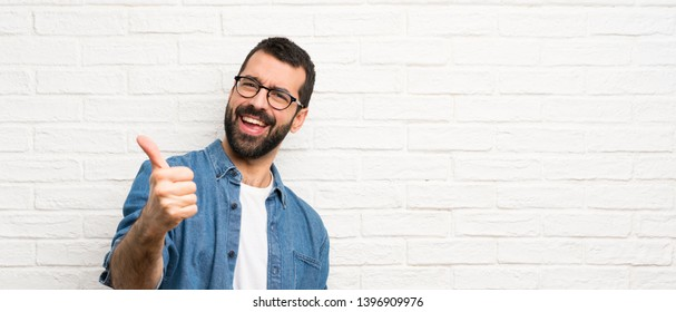 Handsome man with beard over white brick wall with thumbs up because something good has happened