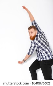 handsome man with beard pointing copy space. young man in plaid shirt showing large size of something