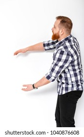 handsome man with beard pointing copy space. young man in plaid shirt pointing away against white wall