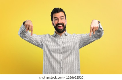 Handsome man with beard pointing down