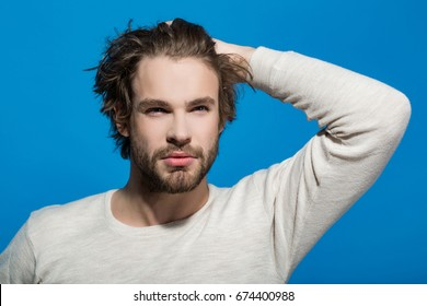 handsome man with beard and stylish hair in white underwear with raised hand on blue background, morning and fashion