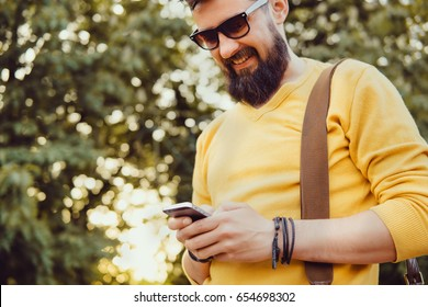 Handsome man beard using smartphone in hand, happy face, street photo, hipster style portrait, backpack, mining bitcoin