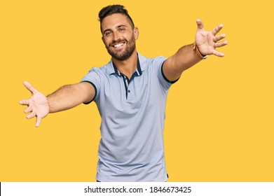 Handsome man with beard wearing casual clothes looking at the camera smiling with open arms for hug. cheerful expression embracing happiness.