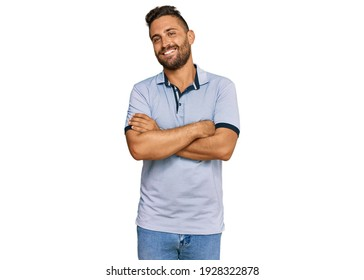 Handsome man with beard wearing casual clothes happy face smiling with crossed arms looking at the camera. positive person.