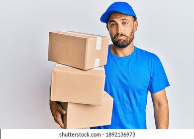 Handsome man with beard wearing courier uniform holding delivery packages depressed and worry for distress, crying angry and afraid. sad expression.
