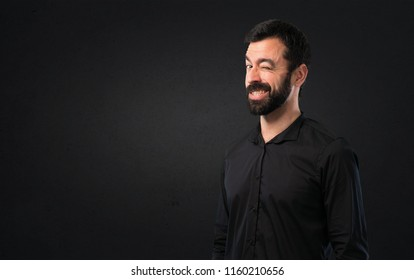 Handsome man with beard winking on black background