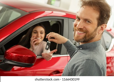 Handsome man with bearded face and  beautiful smile looking at camera. Beautiful woman smiling and receiving keys of red car on background. Man working as manager in car dealership.