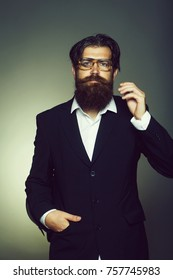 Handsome man bearded hipster male wears vintage glasses black suit on grey wall