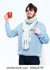 handsome man or bearded sexy guy in blue sweater and scarf shows with finger on coffee or tea cup isolated on white background