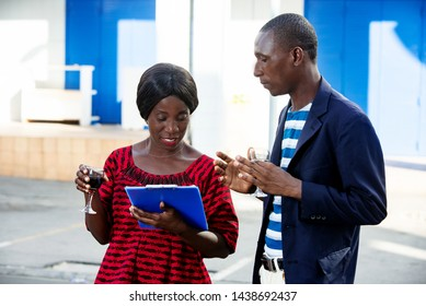 handsome man and beautiful african adult businesswoman standing by discussing project business, holding in hand a blue document and a drink, on the street