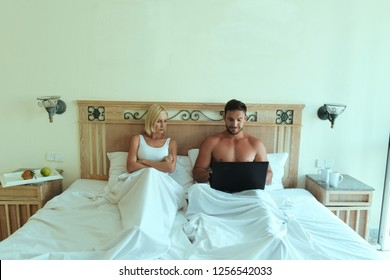 handsome man and beautiful blonde lying in bed together. Wife is upset that his husband always works on his laptop, she is angry of a lack of sex. Woman yells at man because he is busy with notebook