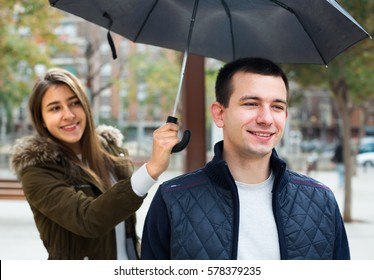 Handsome man and beautiful girl smiling under umbrella outdoors