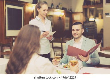Handsome man with beautiful happy girlfriend making order in cafe
