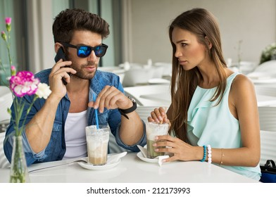 Handsome man with beautiful woman in cafe talking by the smart phone
